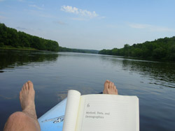 diligently' at work reading in the middle of the St. Croix River